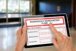 Hands with Computer Tablet completing Emergency Evacuation Plan App by Exit Doors